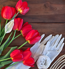 Red tulips and white lace gloves on wooden background