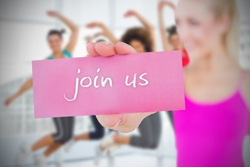 Fit blonde holding card saying join us