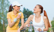 Two smiling girl friends in sports clothing drinking