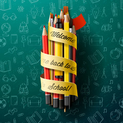 Colorful pencil crayons with text Back to school on ribbon