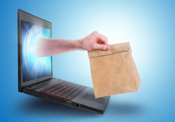 Hand holding a paper bag coming out of a laptop screen