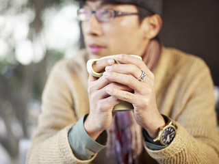 man holding coffee cup looking away