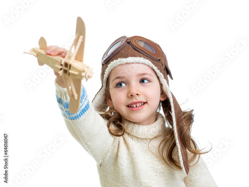 child dressed as pilot and playing with wooden airplane toy isol