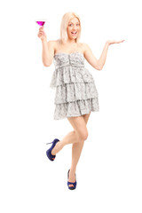 Fashionable girl with cocktail gesturing happiness