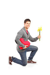 Guy crouching down on his knee with a bunch of tulips