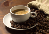 Fototapety coffee cup and grains on wooden table