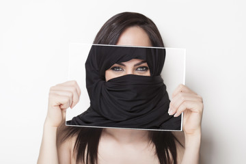 Girl holding a photo of herself wearing a burqa