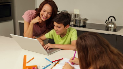 Mother using laptop with son while daughter is drawing