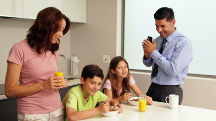 Smiling family at breakfast before father goes to work