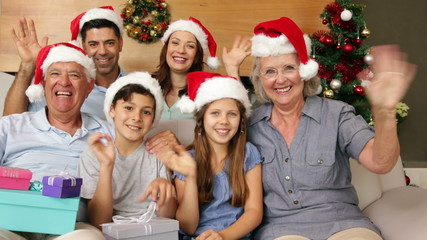 Happy extended family waving at camera at christmas time