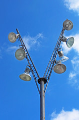 Modern pole with spotlights and blue sky with clouds behind