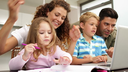 Happy children drawing at the table with their parents and using