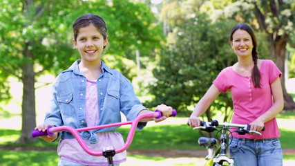 Cute mother and daughter on a bike ride in the park together