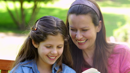 Mother and daughter reading together on a park bench