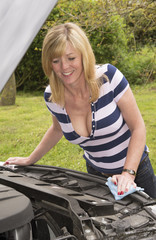 Motorist inspecting the engine compartment of her car