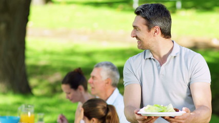 Father offering plate of food to camera at family barbecue