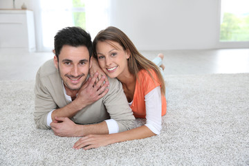 Couple laying on carpet of brand new renovated flat