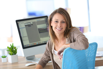 Cheerful business girl in front of desktop computer