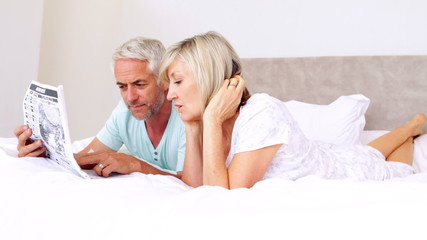 Couple lying on bed reading newspaper together