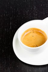 great italian coffee in a white cup on black wood table