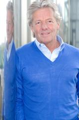 Älterer Mann im blauen Pulli vor Spiegelsäule