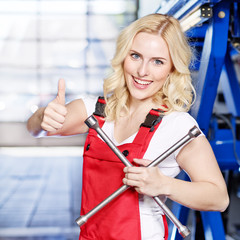 Female apprentices for car mechanic shows thumb up