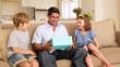 Cute children giving their father presents on the couch