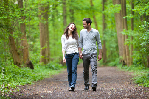Poster Young couple having a walk in a forest