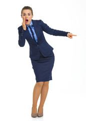 Portrait of shocked business woman pointing on copy space