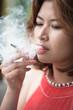 young asian woman smoking cigarette - 64625824