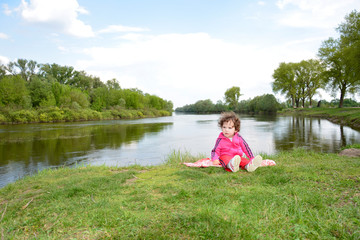 Little girl sitting near the river.