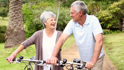 Retired couple standing in the park with their bikes