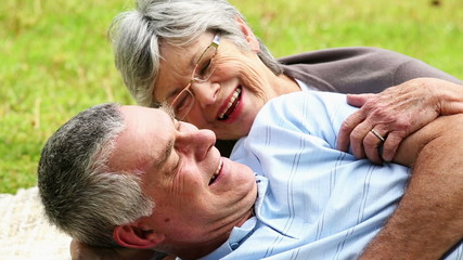 Affectionate senior couple relaxing in the park lying on blanket