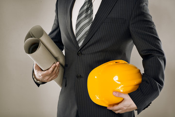 Man architect wearing suit holding blueprint and helmet