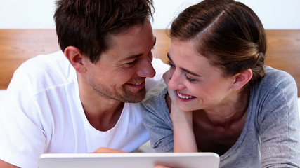 Happy couple lying on bed using tablet together