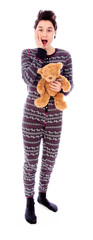 Young woman standing with her teddy bear and looking shocked
