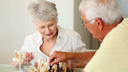 Senior couple sitting at table playing chess