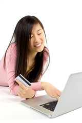 Cute Chinese girl searching to buy online with credit card