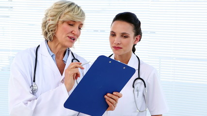 Doctor and nurse discussing something on clipboard