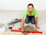 Man laying ceramic floor tiles on concrete floor