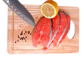 Salmon on wooden board with knife and lemon