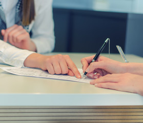 Female hands putting signature to agreement document in office