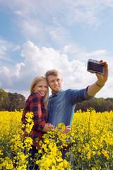 Amorous couple take a photo on a rape field