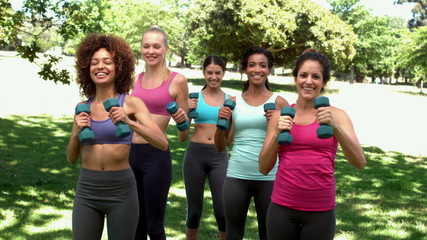 Fitness class working out together with dumbbells in the park