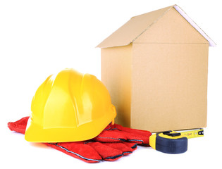 Cardboard house with helmet and gloves isolated on white