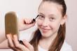 Happy teen girl paints eyelashes