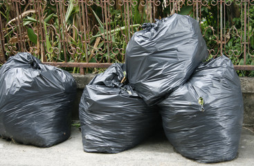 black garbage bags on the ground to await disposal