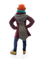 Rear view of a young woman in warm clothing and standing with ar