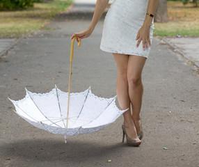 Bride with white umbrella in the park