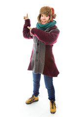 Young woman in warm clothing and pointing backward